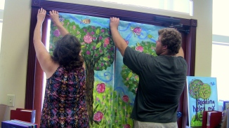 Head librarian Jennifer Wilkins (left) and Mason Holcomb (right) hang up the larger paintings the children made. (Photo by Nan Fairley)