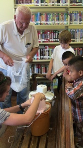 Community partner Myles Smith (standing) and Nathan Simone (left) make homemade ice cream. (Photo by Nan Fairley)
